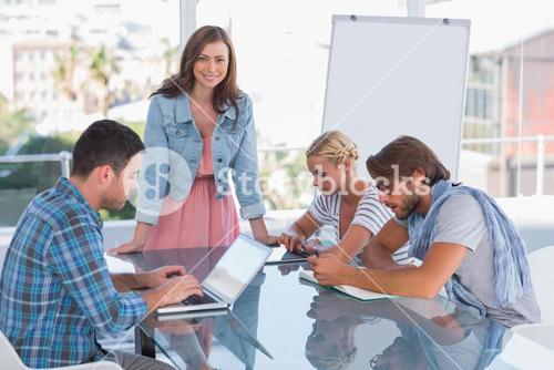 Team having meeting with one woman smiling at camera