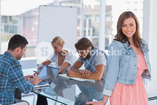 Team having meeting with one woman standing and smiling at camera