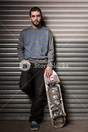 Attractive skater leaning against metal shutters