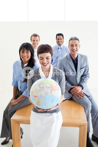 Positive international business people holding a terrestrial globe