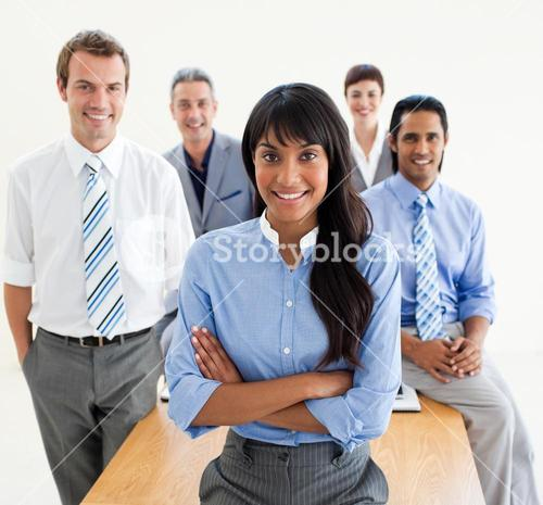 Smiling coworkers standing around a table