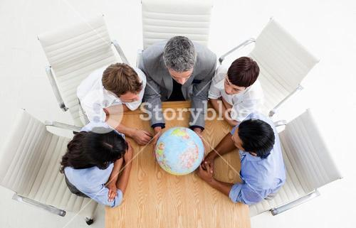 Confident business people around a terrestrial globe