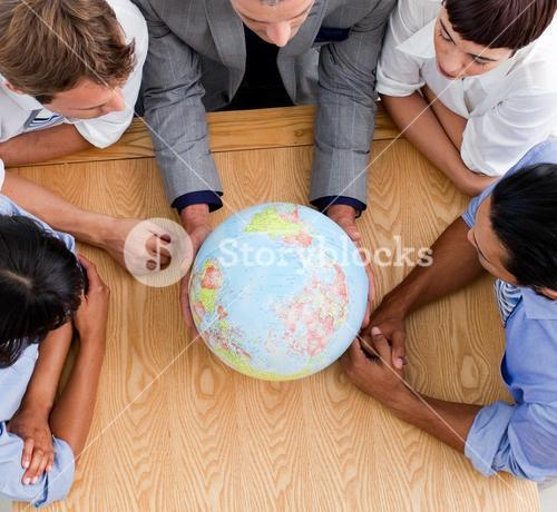 Close up of business people looking at a globe