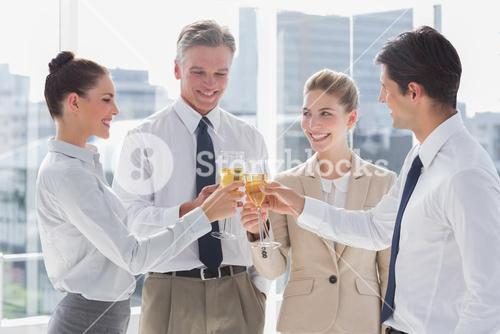 Group of business people clinking their flutes of champagne