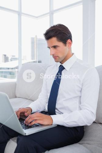 Attractive businessman typing on his laptop