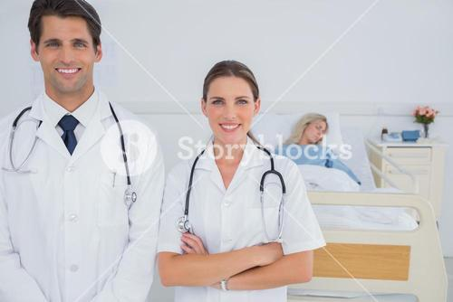 Two doctors standing in front of a hospitalized patient