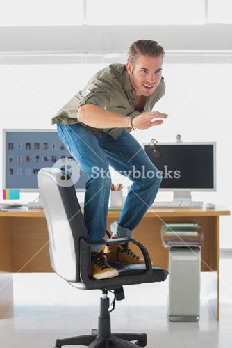 Handsome man surfing his office chair