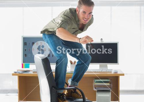 Smiling man surfing his office chair