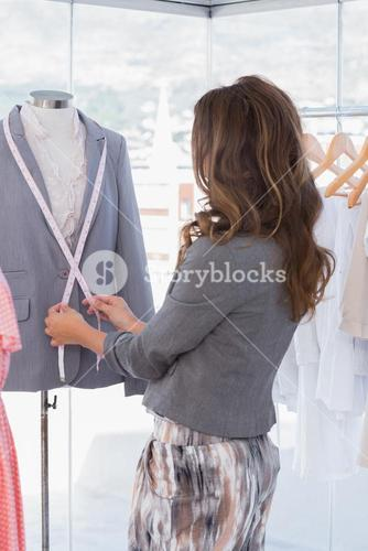 Fashion designer measuring blazer lapel