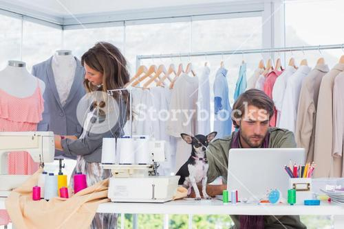 Fashion designers at work with a puppy on the desk
