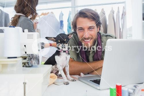 Smiling fashion designer with his chihuahua