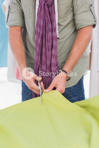Fashion designer cutting green textile