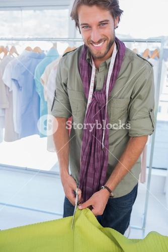 Smiling fashion designer cutting textile