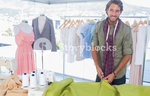 Handsome fashion designer cutting textile