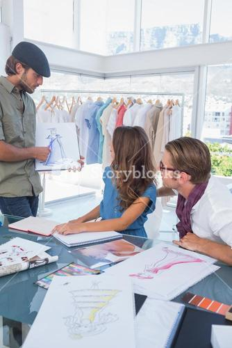 Fashion designer showing a draw to his colleague