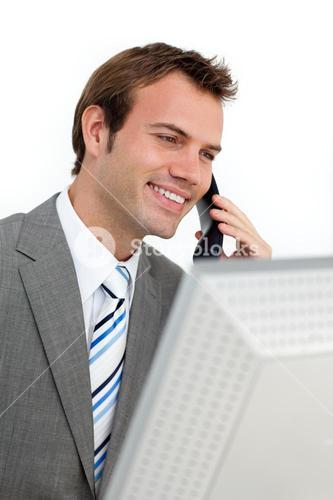 Charming businessman on phone at a computer