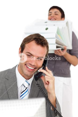 Businesswoman bringing a stack of folders to her colleague