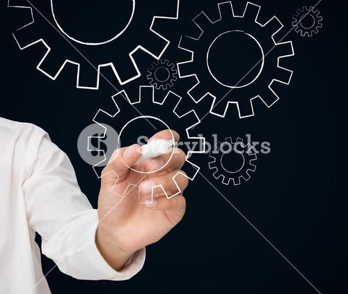 Businessman drawing white cogs and wheels