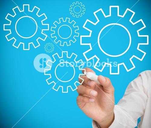 Businessman drawing wheels and cogs
