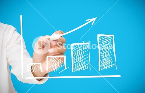 Businessman drawing white arrow above graph