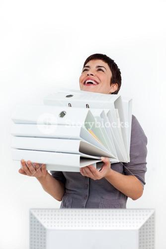 Laughing businesswoman carrying a pile of folders