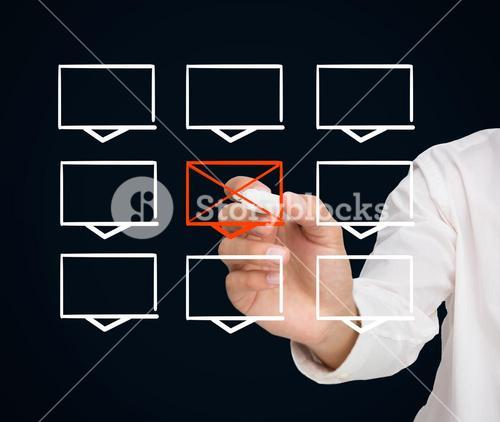 Businessman drawing a cross through a rectangle in a grid