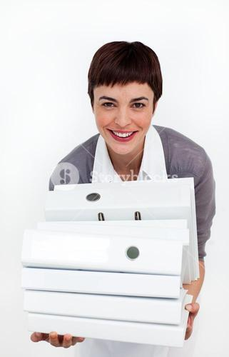 Smiling businesswoman putting a stack of folders on a desk
