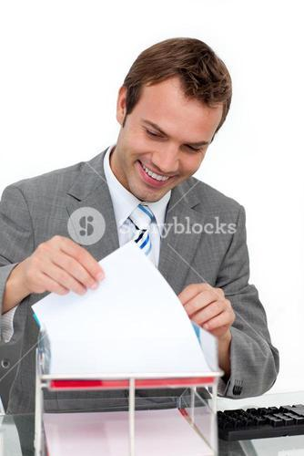 Smiling young businessman studying a document