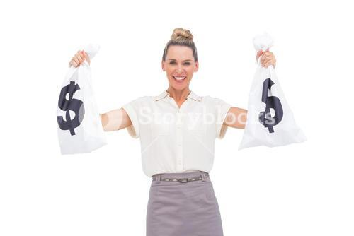 Smiling businesswoman holding money bags