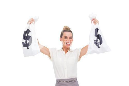 Smiling businesswoman carrying money bags