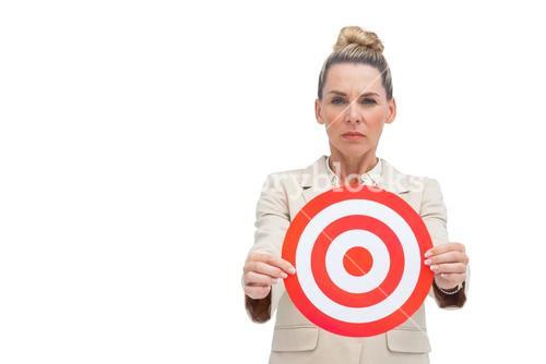 Frowning businesswoman holding target