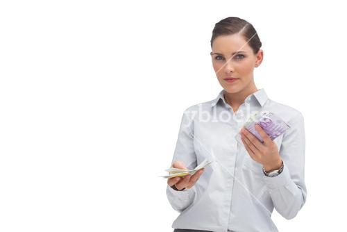 Businesswoman holding wads of cash and looking at camera