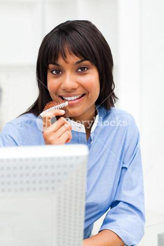 Smiling businesswoman eating a muffin