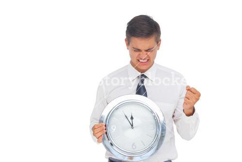 Excited businessman holding a clock