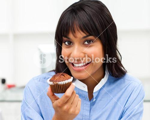 Close up of a young businesswoman eating a muffin