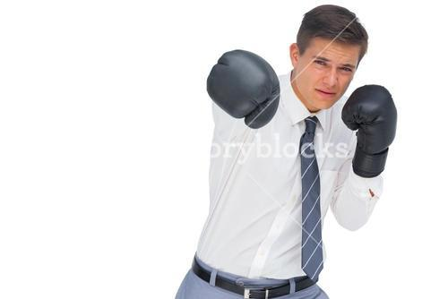 Businessman punching with black boxing gloves