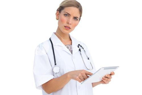 Annoyed nurse using tablet pc