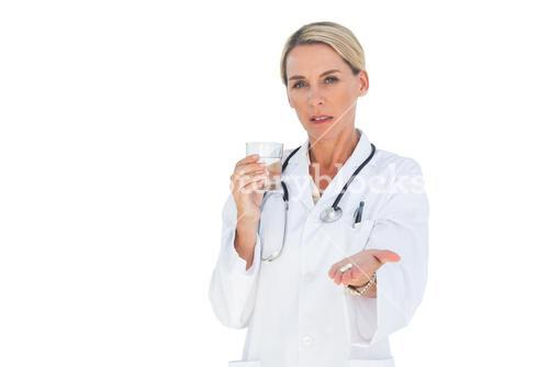 Stern doctor with medication and a glass of water in her hands