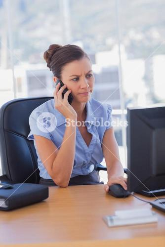 Concentrating businesswoman working on her computer and calling