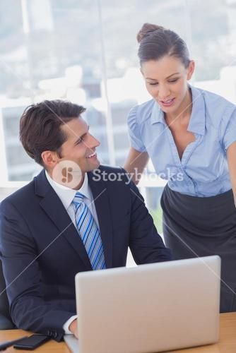 Happy business people working together with a laptop and smiling