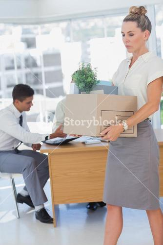 Businesswoman holding a box and his colleagues in the bottom