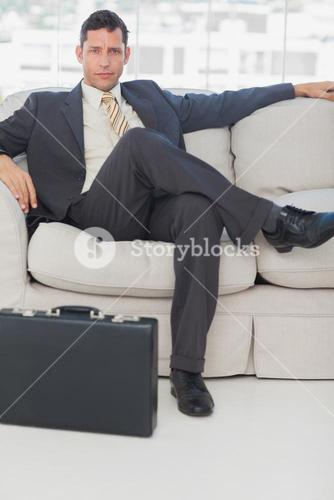 Businessman sitting with legs crossed on the couch