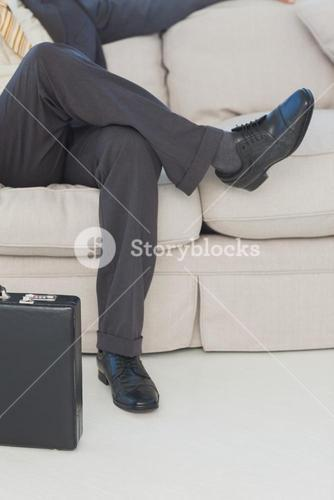 Businessman with legs crossed on couch