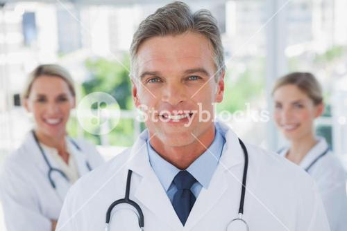 Charismatic doctor standing with colleagues