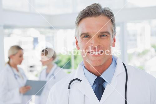 Smiling grey haired doctor standing in his office