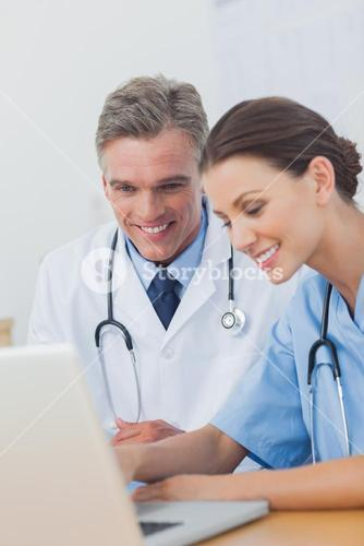 Two cheerful doctors working on a laptop