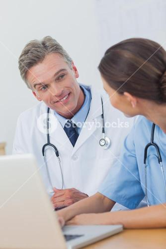 Two smiling doctors working on a laptop