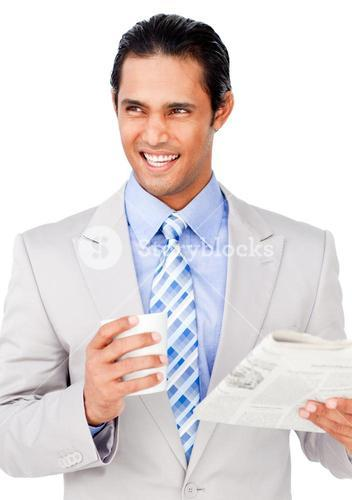 Confident businessman driking coffee while reading a newspaper