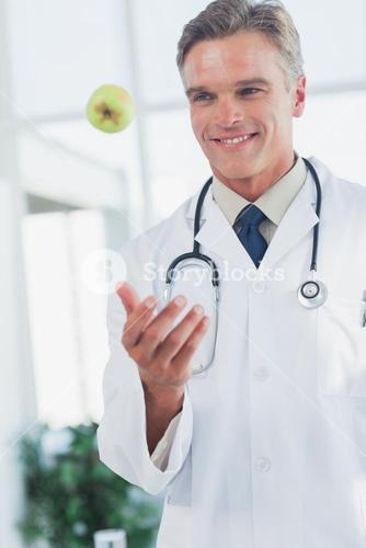 Doctor throwing a green apple