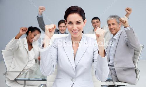 Happy business people celebrating a sucess with hands up